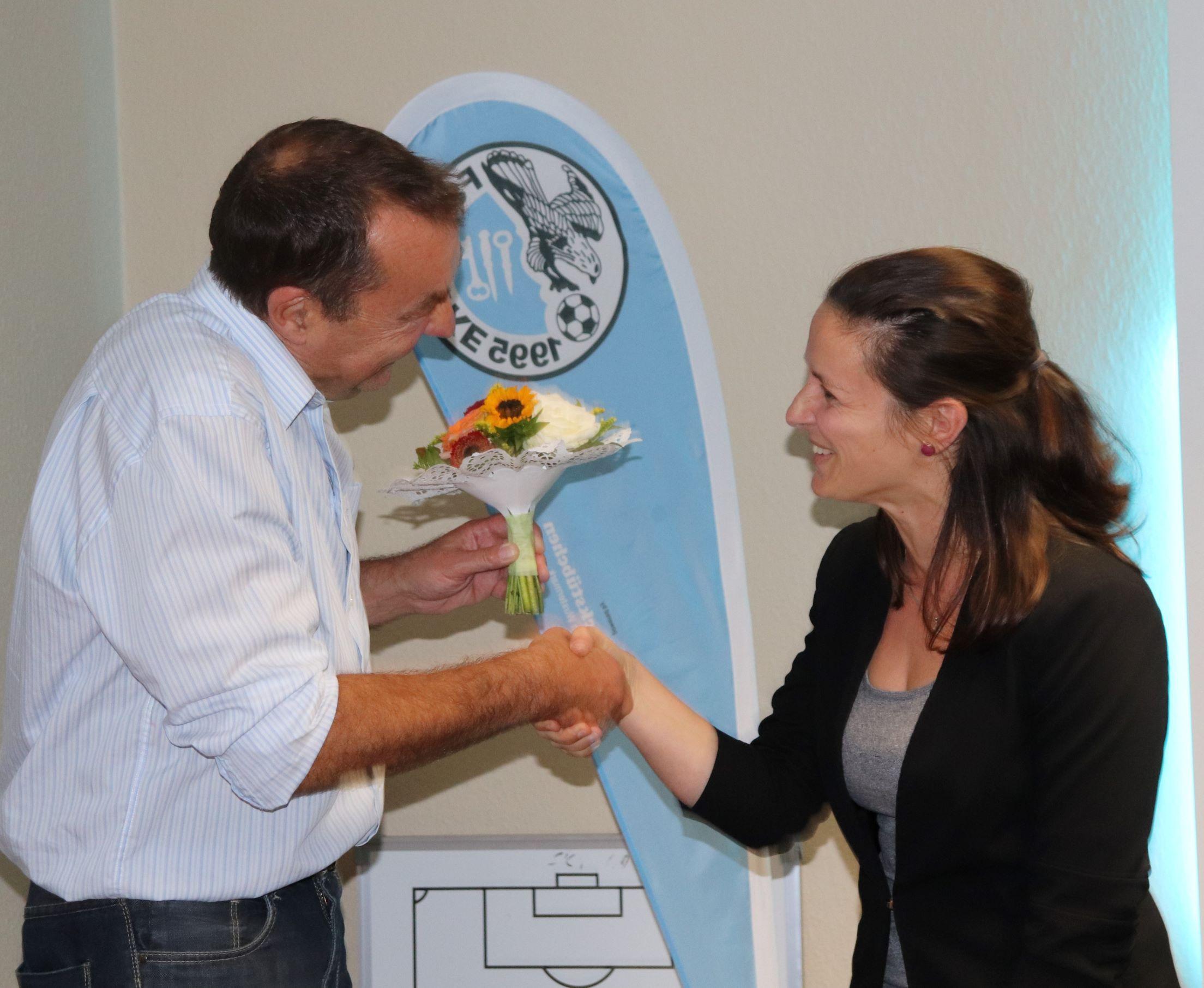 Übertrieben theatralisch übergibt Frank Recknagel einen Blumenstrauß an das neugewählte Vorstandsmitglied Corinna Stackebrandt