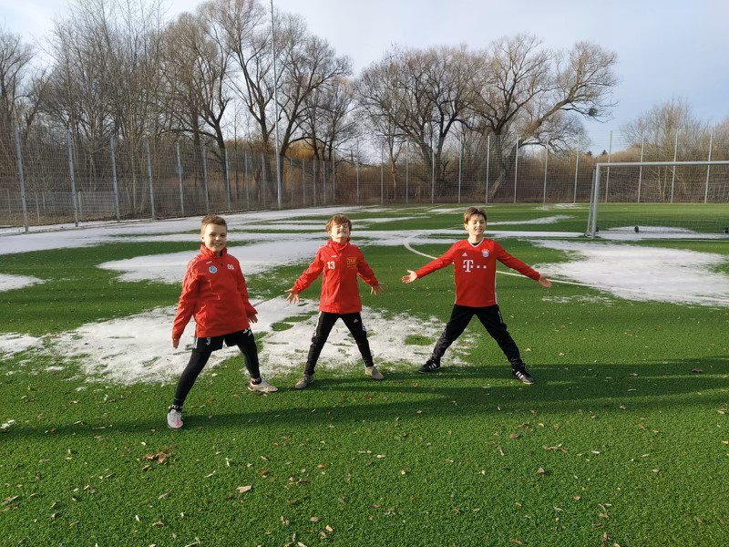 Drei Fussballkinder halten den Corona-Abstand